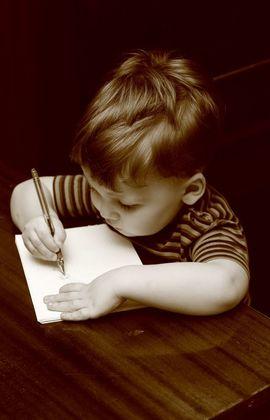 мальчик рисует на листе бумаги