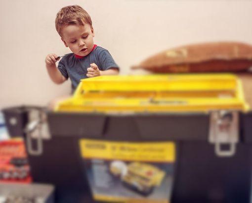 мальчик разбирает ящик с инструментами